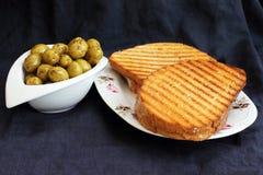 Rösten Sie gebratenes Brot und grüne Oliven, Frühstück in einem Mediterrane Stockbild