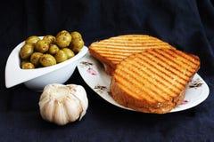 Rösten Sie gebratenes Brot und grüne Oliven, Frühstück in einem Mediterrane Lizenzfreies Stockfoto