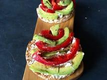 Rösten Sie mit Avocado, Pfeffer und Käse auf farbigem konkretem Hintergrund Stockfotografie