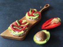 Rösten Sie mit Avocado, Pfeffer und Käse auf farbigem konkretem Hintergrund Stockfotos