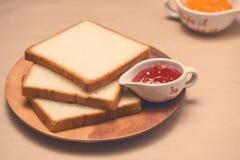 Rösten Sie mit Erdbeere und Orangenmarmelade auf einer Platte auf Tabelle Lizenzfreie Stockfotos