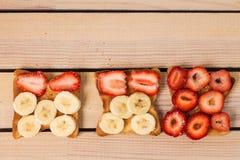 Rösten Sie mit Erdbeeren und Bananen auf einem hölzernen Hintergrund Stockfotos