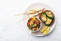 Rösten Sie mit Zucchinigrill und Salat von Oliven, Gurken, Tomate, süße rote Zwiebel, gelber Paprikapfeffer mit gegrillt Lizenzfreies Stockfoto