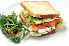 Rösten Sie Sandwich mit Lachsen, Gemüse und Salat auf weißer Platte Stockfotos