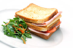 Rösten Sie Sandwich mit Schinken, Käse, Tomaten und Salat auf weißer Platte, auf weißem Hintergrund Stockfotografie