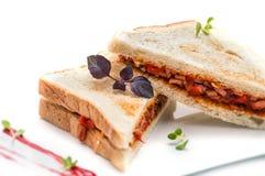 Rösten Sie Sandwich mit Schinken, Tomaten auf der weißen Platte, lokalisiert auf weißem Hintergrund Lizenzfreies Stockbild
