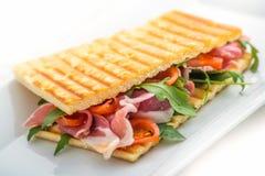 Rösten Sie Sandwich mit Schinken, Tomaten und Arugulasalat auf weißer Platte Stockfotos