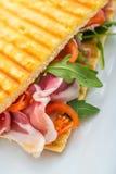 Rösten Sie Sandwich mit Schinken, Tomaten und Arugulasalat auf weißer Platte Lizenzfreie Stockfotos