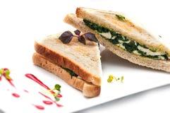 Rösten Sie Sandwich mit Spinat, Tofu und Käse auf der weißen Platte, lokalisiert auf weißem Hintergrund Lizenzfreie Stockbilder