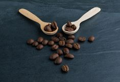 Röstkaffee-Bohnen und zwei kleine hölzerne Löffel lizenzfreie stockfotos