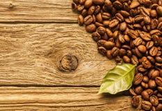 Röstkaffeebohnen auf strukturiertem rustikalem Holz Stockfotos