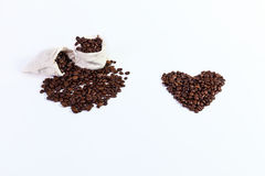 Röstkaffeebohnen in einem Lappen bauscht sich, Röstkaffeebohnen auf einem wh Lizenzfreie Stockbilder