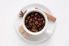 Röstkaffeebohnen in einer Kaffeetasse verzierten Gewürze und Zucker gegen weißen Hintergrund, Draufsicht mit Raum für Text Stockfotos