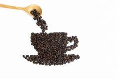 Röstkaffeebohnen an gesetzt in Form einer Tasse und Untertasse Lizenzfreies Stockbild