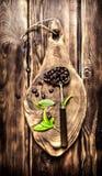 Röstkaffeebohnen im alten Löffel auf einem hölzernen Brett Lizenzfreie Stockbilder
