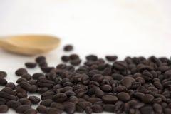Röstkaffeebohnen und ein hölzerner Löffel auf weißem Hintergrund Lizenzfreie Stockfotografie