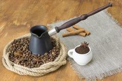 Röstkaffeebohnen und Sternanis in einem Ring des Hanfs, in der Mitte des cezve nahe bei einer Leinenserviette mit Kaffeetasse und lizenzfreie stockbilder