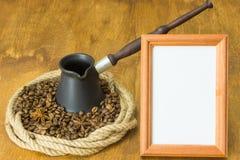 Röstkaffeebohnen und Sternanis in einem Ring des Hanfs, in der Mitte des cezve und des weißen Rahmens für Ihren Aufkleber Stockbild