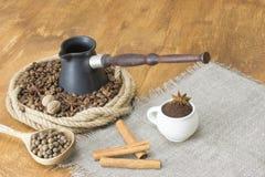 Röstkaffeebohnen und Sternanis in einem Ring des Hanfs, in der Mitte des Türken nahe bei einer Leinenserviette mit Kaffeetasse un Lizenzfreie Stockbilder