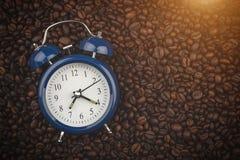 Röstkaffeebohnen und -Wecker Wachen Sie auf Guten Morgen Hintergrund, Großaufnahme stockfotos