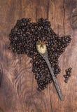Röstkaffeebohnen vereinbarten in Form Afrikas auf altem Holz Lizenzfreie Stockfotos