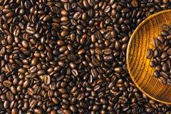Röstkaffeebohnenhintergrund und -beschaffenheit mit hölzerner Platte, Co Stockbild