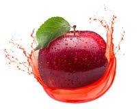 Rött äpple i fruktsaftfärgstänk som isoleras på en vit bakgrund arkivbild