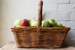 Rött äpple i korgen av gröna äpplen Arkivfoto