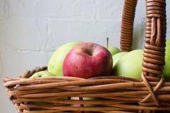 Rött äpple i korgen av gröna äpplen (nära övre) Arkivfoto