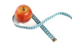 Rött äpple i måttbandet som isoleras på vit Arkivfoton