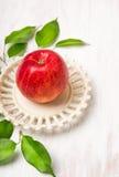 Rött äpple i tappningplatta med sidor på vitt trä Royaltyfri Foto