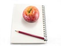 Rött äpple med anteckningsboken arkivbild
