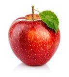 Rött äpple med det gröna bladet som isoleras på en vit Arkivfoto
