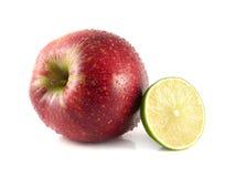 rött äpple med halva av limefrukt på en vit Royaltyfria Foton