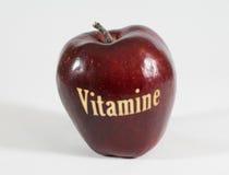 Rött äpple med ordet - vitaminer - i tyskt språk Arkivbild