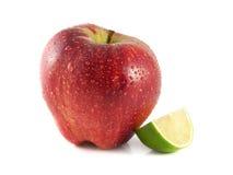 rött äpple med skivad limefrukt på vit royaltyfria foton