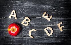 Rött äpple och alfabet som göras av träbokstäver på en mörk bakgrund av en skolförvaltning 9 barn för lärare för leende för skola arkivfoton