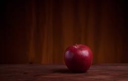Rött äpple på en grungeträ- och apelsinbakgrund Fotografering för Bildbyråer