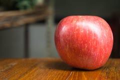 rött äpple på en trätabellstilleben Royaltyfri Bild
