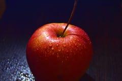 Rött äpple på svart bakgrundsslut upp royaltyfri bild
