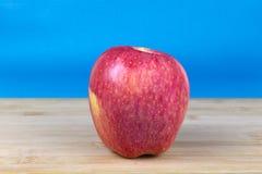 Rött äpple på träyttersida med blå bakgrund royaltyfri foto