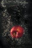 Rött äpple som faller in i vatten Royaltyfri Fotografi