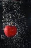 Rött äpple som faller in i vatten Royaltyfri Foto