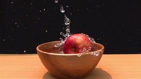 Rött äpple som faller in i vattnet i en träbunke lager videofilmer