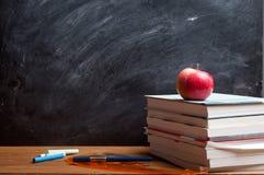 Rött äpple som vilar på boken Royaltyfria Foton