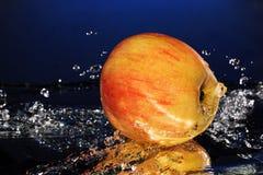 Rött äpple under en vattenfall som plaskar på den blåa bakgrundsspegeln Arkivbild