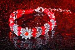 Rött armband med droppar av vatten arkivfoton