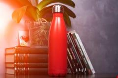 Rött av den thermo flaskan för färg över bakgrund av böcker och den gröna blomman Med solljuseffekt arkivbild
