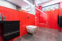 Rött badrum med toaletten arkivbild