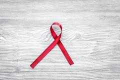 Rött band för HIV, HJÄLPMEDEL, drogmissbruk och anoreximedvetenhet på bästa sikt för grå träbakgrund Arkivbild
